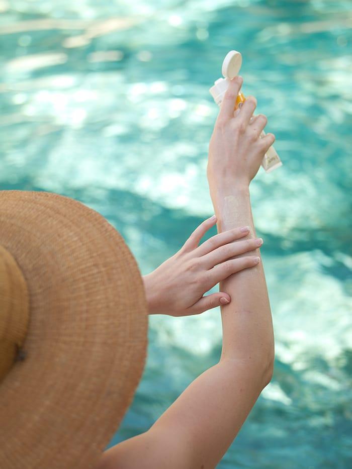 Woman in hat rubbing sunscreen onto skin.